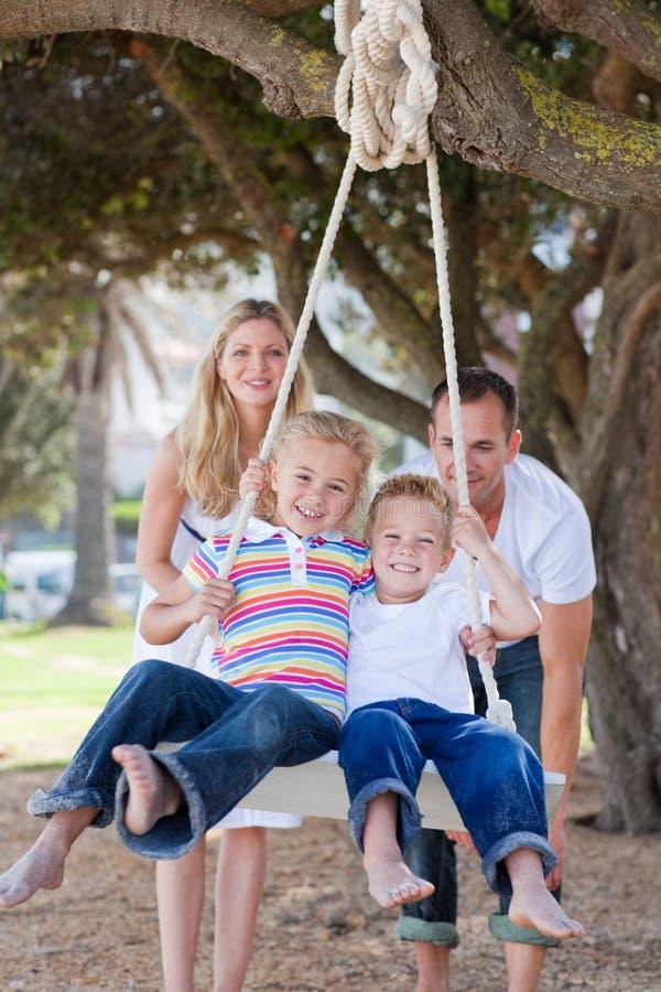 Frohe Muttergesellschaft, die ihre Kinder auf einem Schwingen drücken lizenzfreie stockbilder