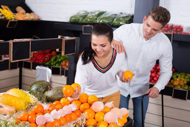 Frohe Paare, die auf Früchten im Shop entscheiden stockbild