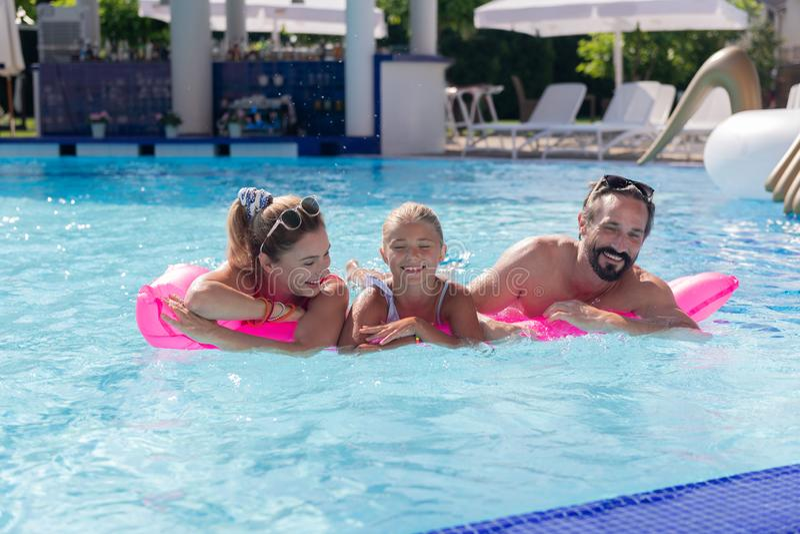 Frohe positive Familie, die Spaß im Pool hat stockfotografie
