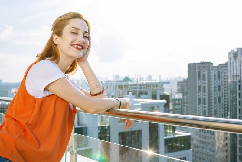 Frohe positive Frau, die auf dem Balkon steht lizenzfreie stockbilder
