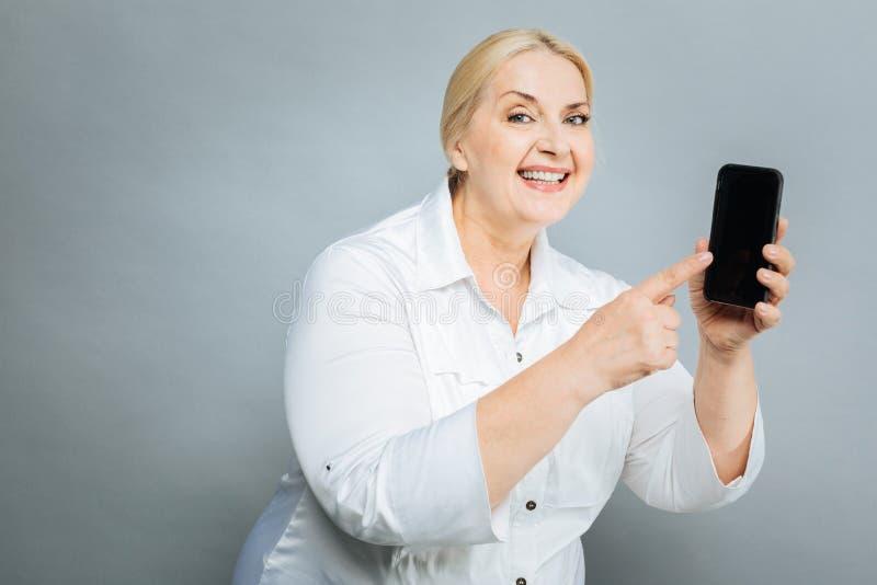 Frohe reife Frau, die auf Telefon zeigt stockbilder