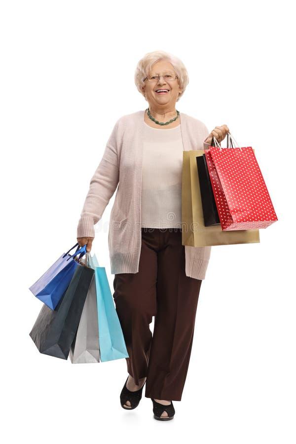 Frohe reife Frau mit Einkaufstaschen gehend in Richtung zum camer stockfotografie