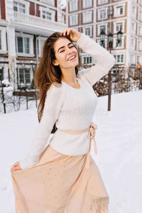 Frohe reizend junge Frau in der weißen woolen Strickjacke und im hellen beige Rock kaltes Winterwetter genießend Zeit des Schnees lizenzfreie stockbilder