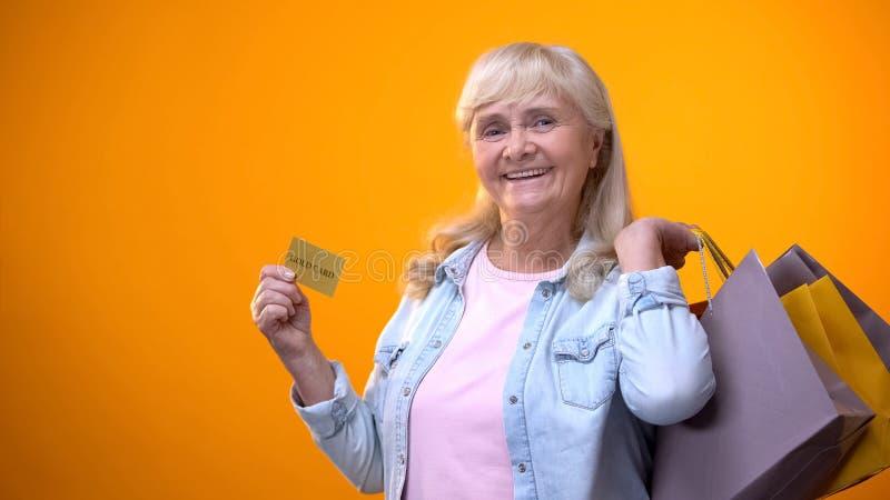 Frohe Rentnerdame, die Einkaufstaschen und goldene Karte, Dauerkunden zeigt stockfotos