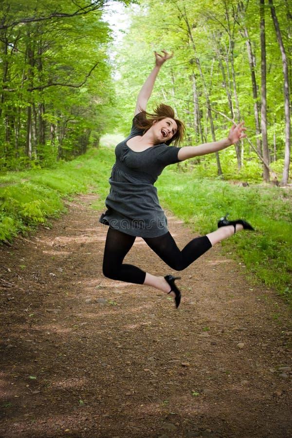 Frohe springende Frau stockbilder