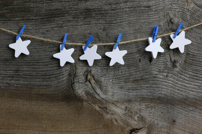 Frohe Weihnacht-hängende Dekorations-weiße hölzerne Sterne und blaues C lizenzfreie stockfotos
