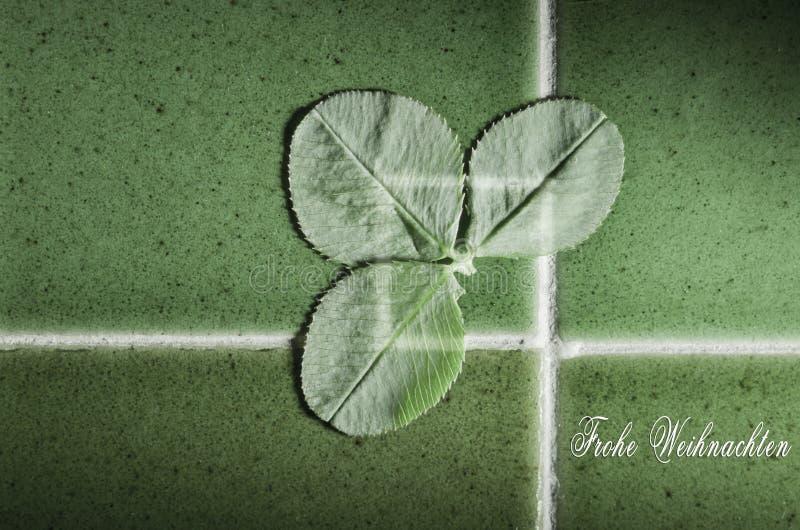 Frohe Weihnachten用与绿色三叶草的德语写的圣诞快乐在好运绿色铺磁砖背景 免版税图库摄影