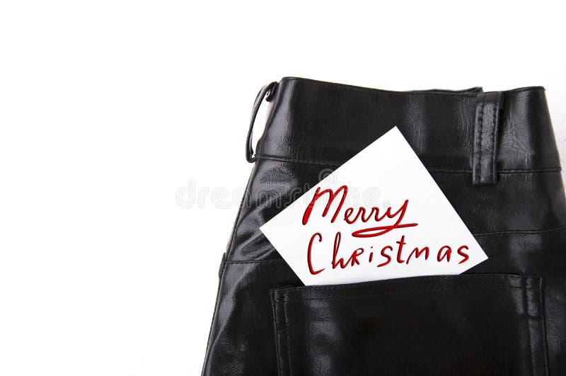 Frohe Weihnachten auf Weißbuch in der Tasche der ledernen Hose stockbild