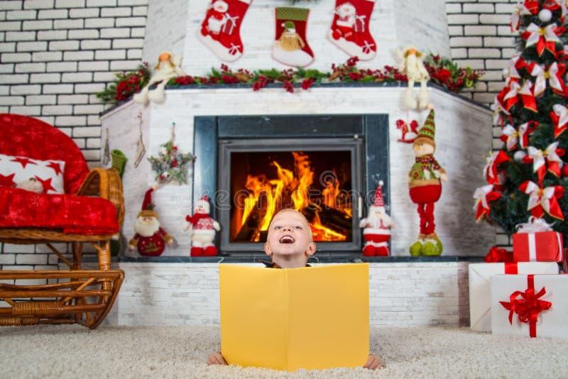 Frohe Weihnachten! Ein kleiner Junge sitzt nahe einem Weihnachtsbaum und einem Kamin und liest ein Buch mit neues Jahr ` s Geschi lizenzfreie stockbilder