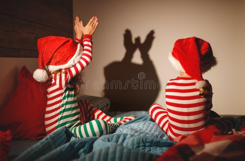 Frohe Weihnachten Kinder spielen Schattentheater im Bett stockfotos