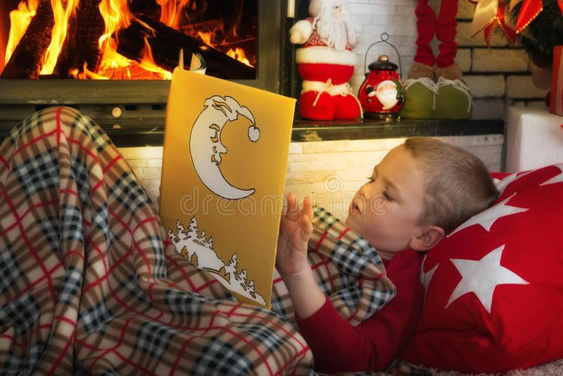 Frohe Weihnachten! Netter Junge, der ein Buch liegt auf dem Teppich nahe dem Kamin liest lizenzfreies stockbild