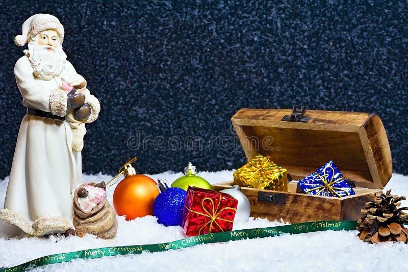 Frohe Weihnachten - Santa Claus-Zahl mit einer Holzkiste voll von den Geschenken und von einem Abendschneehintergrund lizenzfreies stockfoto