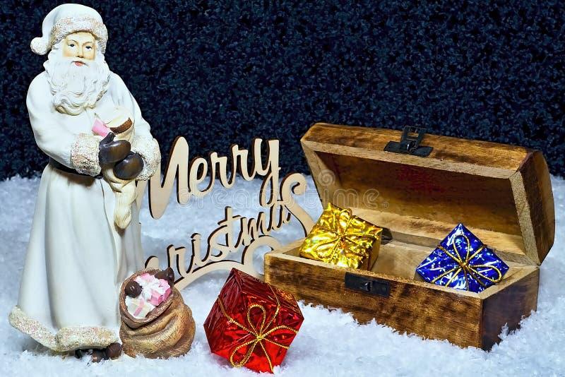 Frohe Weihnachten - Santa Claus-Zahl mit einer Holzkiste voll von den Geschenken und von einem Abendschneehintergrund stockfoto