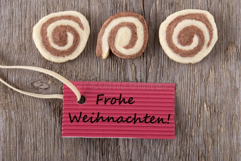 Frohe Weihnachten. Some cookies and a maker tag with the german words Frohe Weihachten, which means merry christmas as background royalty free stock photos