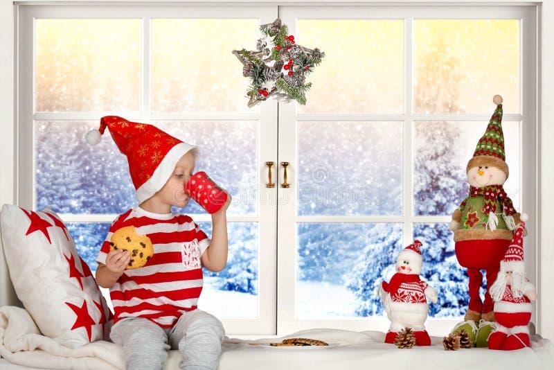 Frohe Weihnachten und frohe Feiertage! Ein kleines Kind, das auf dem Fenster isst Plätzchen und Trinkmilch sitzt lizenzfreies stockfoto