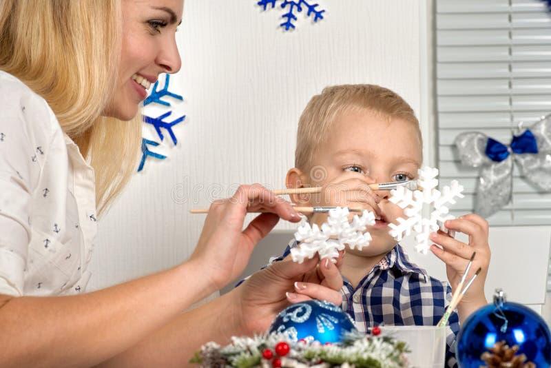 Frohe Weihnachten und frohe Feiertage! Mutter und Sohn, die eine Schneeflocke malen Familie stellt Dekorationen für Weihnachtsinn stockbilder