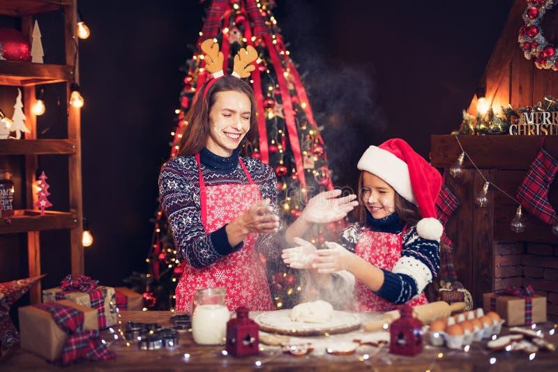 Frohe Weihnachten und frohe Feiertage Mutter und Tochter, die Weihnachtsplätzchen kochen lizenzfreies stockbild