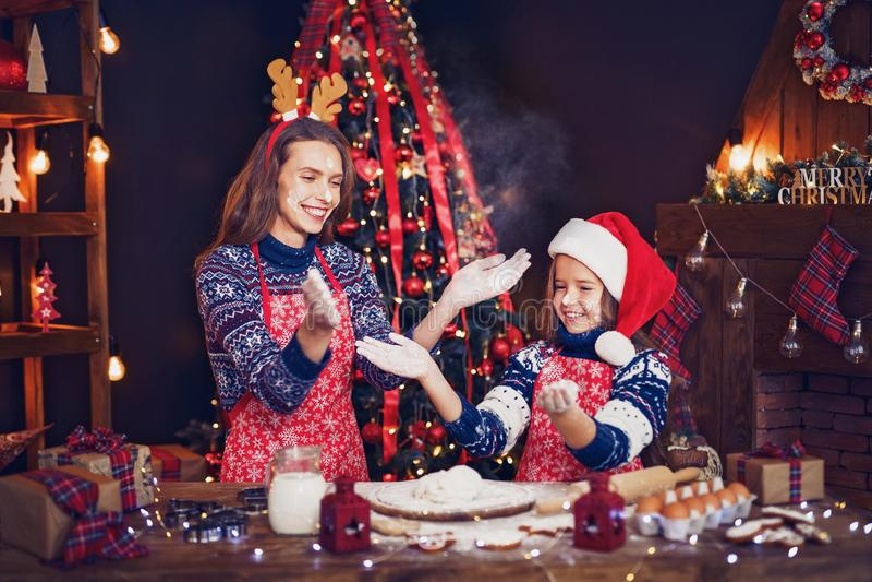 Frohe Weihnachten und frohe Feiertage Mutter und Tochter, die Weihnachtsplätzchen kochen lizenzfreie stockfotos