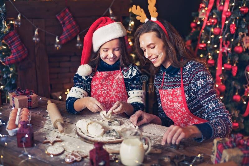 Frohe Weihnachten und frohe Feiertage Mutter und Tochter, die Weihnachtsplätzchen kochen stockfotografie