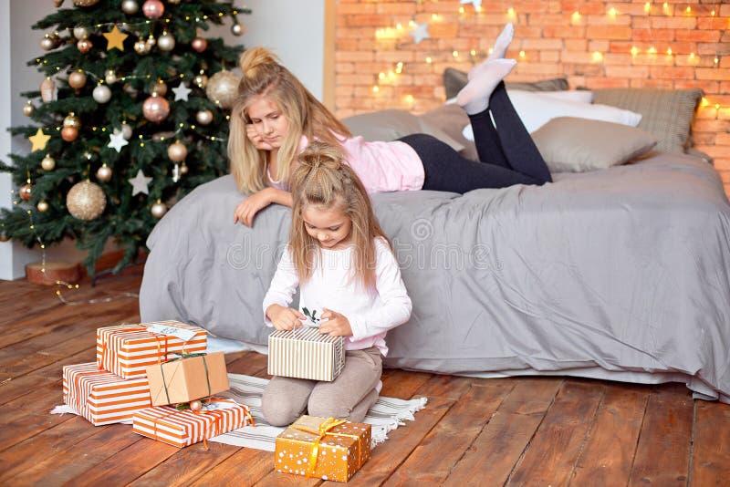 Frohe Weihnachten und frohe Feiertage Nette nette Kinder, die Geschenke öffnen Kinder, die Spaß nahe Baum morgens haben stockbilder