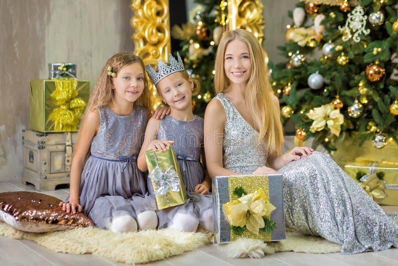 Frohe Weihnachten und frohe Feiertage nette kleines Kindermädchen, die zuhause den weißen grünen Weihnachtsbaum mit vielen Gesche stockbilder