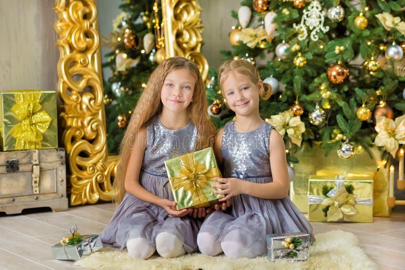 Frohe Weihnachten und frohe Feiertage nette kleines Kindermädchen, die zuhause den weißen grünen Weihnachtsbaum mit vielen Gesche lizenzfreies stockbild