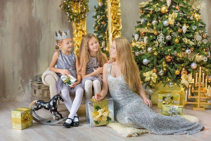 Frohe Weihnachten und frohe Feiertage nette kleines Kindermädchen, die zuhause den weißen grünen Weihnachtsbaum mit vielen Gesche lizenzfreie stockfotografie
