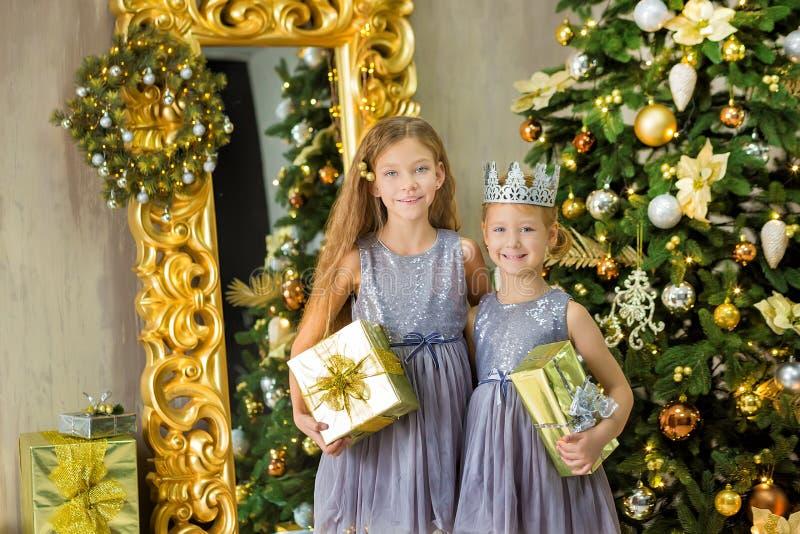 Frohe Weihnachten und frohe Feiertage nette kleines Kindermädchen, die zuhause den weißen grünen Weihnachtsbaum mit vielen Gesche lizenzfreie stockbilder