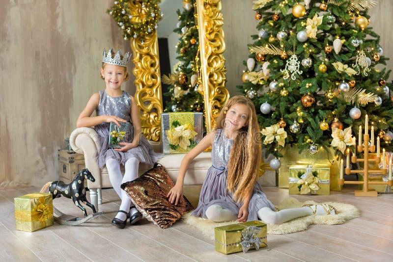 Frohe Weihnachten und frohe Feiertage nette kleines Kindermädchen, die zuhause den weißen grünen Weihnachtsbaum mit vielen Gesche lizenzfreie stockfotos