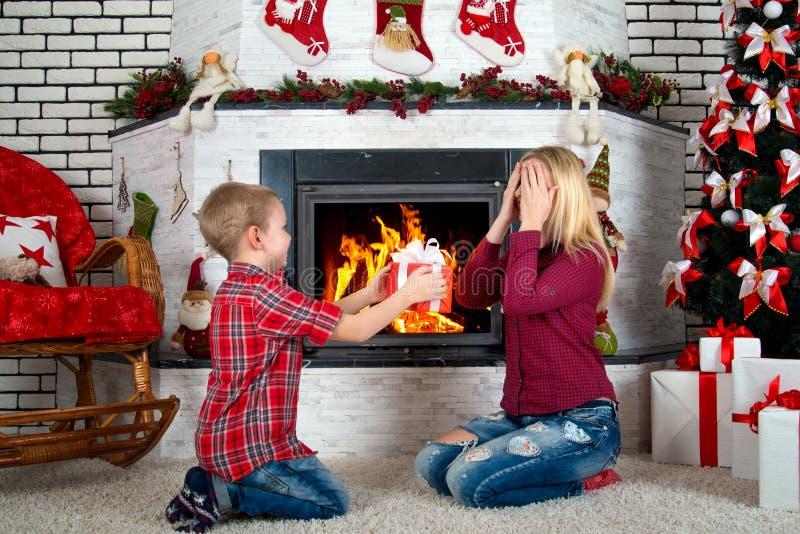 Frohe Weihnachten und frohe Feiertage! Netter Sohn gibt seiner geliebten Mutter ein Geschenk, Überraschung Der Innenraum des neue lizenzfreies stockfoto