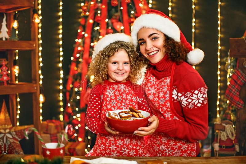Frohe Weihnachten und frohe Feiertage Nettes nettes gelocktes kleines Mädchen und ihre ältere Schwester beim Sankt-Hutkochen lizenzfreies stockfoto