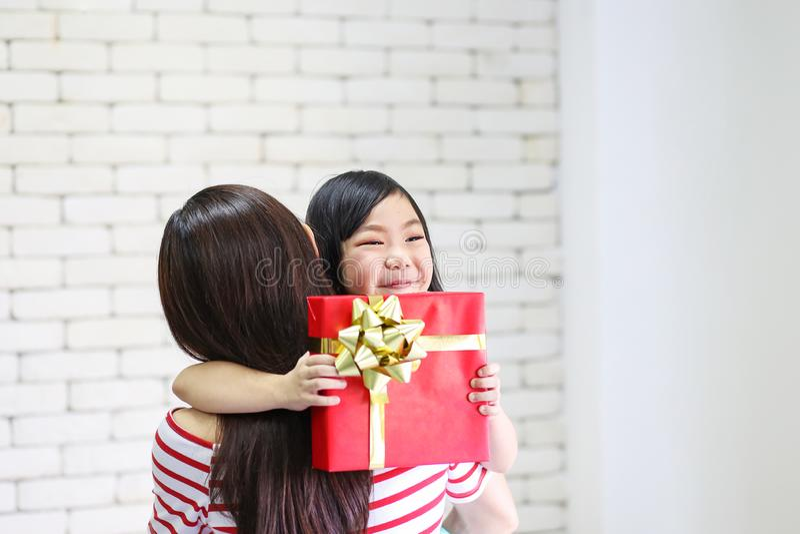 Frohe Weihnachten und frohe Feiertage oder guten Rutsch ins Neue Jahr Mutter gibt den Kindern Geschenke Nettes M?dchen gibt seine stockfoto