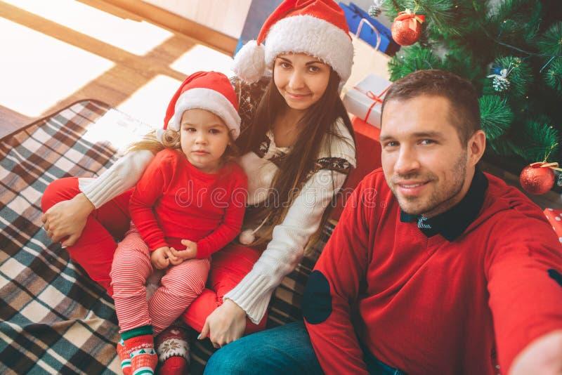 Frohe Weihnachten und guten Rutsch ins Neue Jahr Bild der netten Familie Griffkamera des jungen Mannes und Nehmen selfie Alle wer lizenzfreie stockfotos
