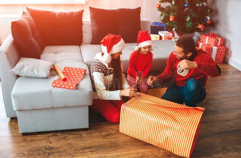 Frohe Weihnachten und guten Rutsch ins Neue Jahr Familie sitzen auf Boden nahe großem Kasten des Geschenkes Junger Mann zeigt sei lizenzfreie stockfotografie