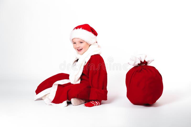 Frohe Weihnachten und guten Rutsch ins Neue Jahr! Netter glücklicher kleiner Junge sitzen wi lizenzfreie stockfotografie