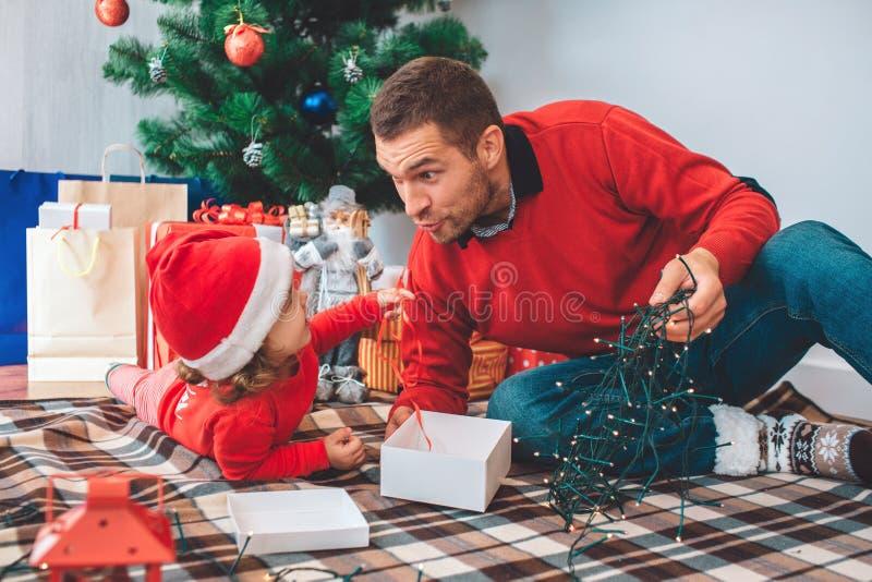 Frohe Weihnachten und guten Rutsch ins Neue Jahr Nettes Bild des Elternteils und des Kindes auf Decke Mädchen liegt auf Magen Man stockfotografie