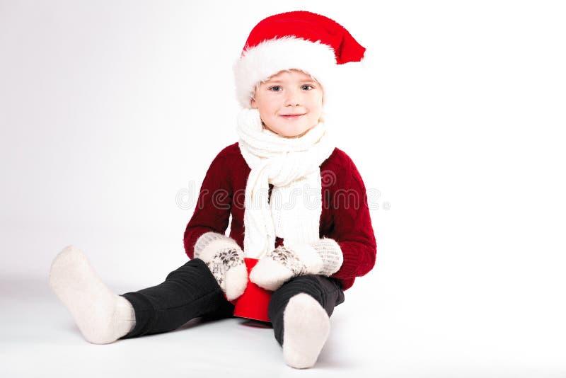 Frohe Weihnachten und guten Rutsch ins Neue Jahr! Nettes glückliches kleiner Junge holdin lizenzfreies stockbild