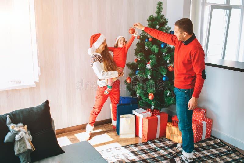 Frohe Weihnachten und guten Rutsch ins Neue Jahr Schönes und helles Bild der jungen Familie stehend am Weihnachtsbaum Manngriffe stockbilder