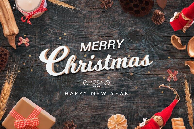 Frohe Weihnachten und guten Rutsch ins Neue Jahr simsen auf schwarzem hölzernem Schreibtisch mit Weihnachtsdekorationen lizenzfreies stockbild