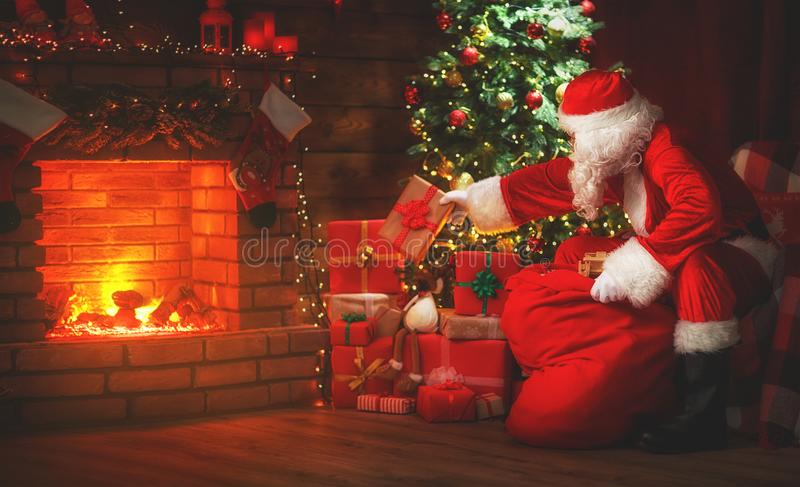 Frohe Weihnachten! Weihnachtsmann nahe dem Kamin und dem Baum mit Gi stockfotos