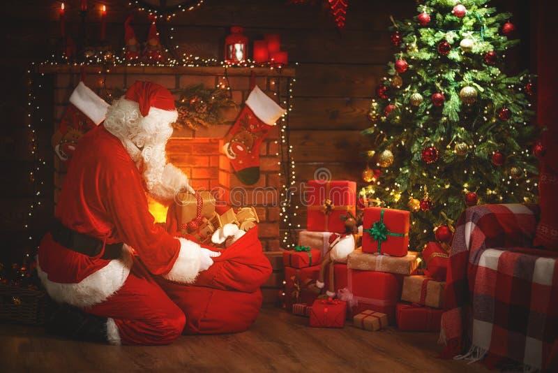 Frohe Weihnachten! Weihnachtsmann nahe dem Kamin und dem Baum mit Gi