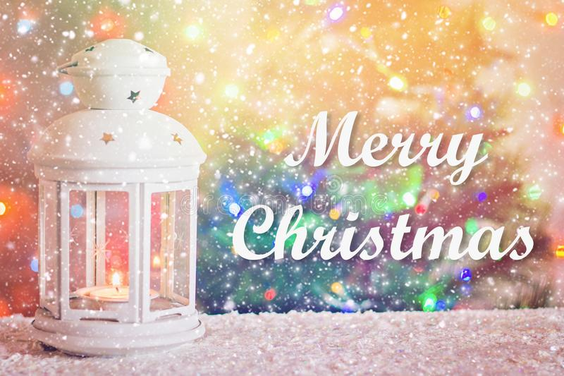 Frohe Weihnachten Weihnachtsweiße Laterne mit einer brennenden Kerze auf dem Hintergrund eines Weihnachtsbaums, Lichter von Girla lizenzfreie stockfotografie