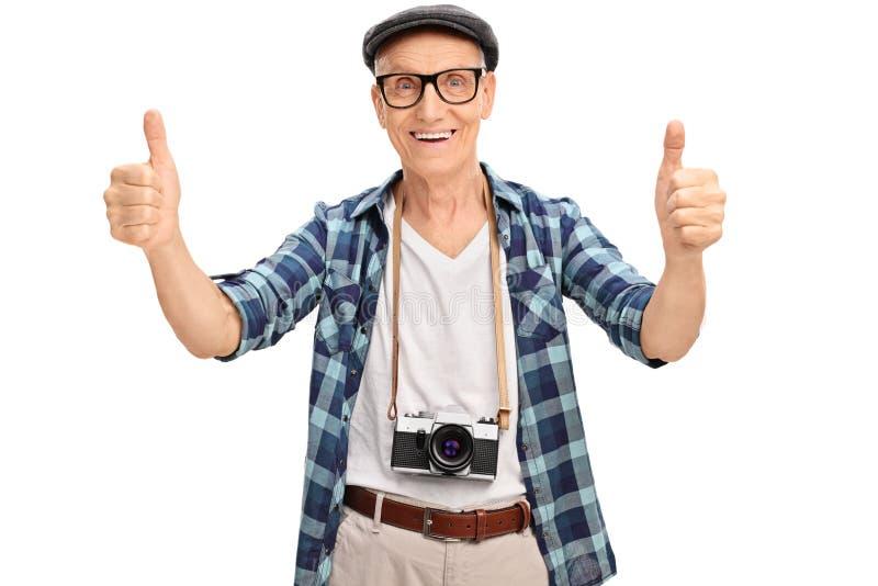 Froher älterer Tourist, der zwei Daumen aufgibt lizenzfreie stockbilder