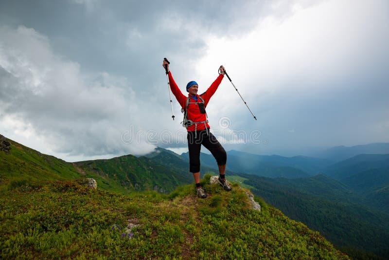Froher Abenteurer steht auf der Klippe mit den offenen Armen lizenzfreies stockfoto