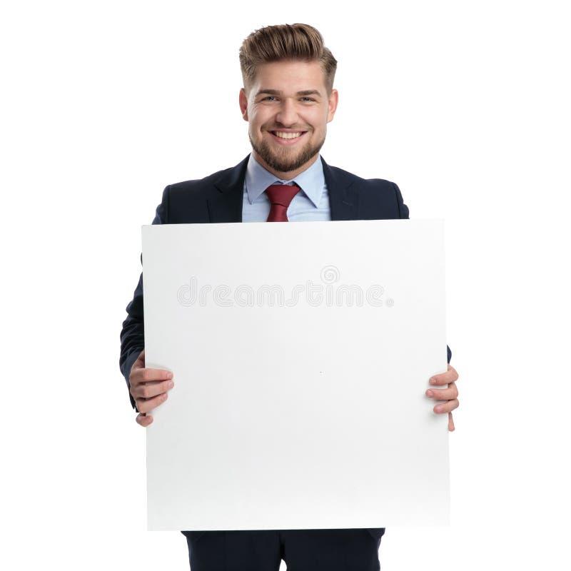 Froher Geschäftsmann, der eine leere Anschlagtafel und ein Lachen hält stockbilder