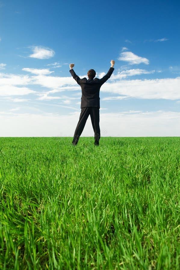 Froher Geschäftsmann, der am grünen Gras steht stockfotos