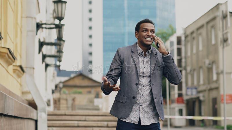 Froher Geschäftsmann des Afroamerikaners glücklich nach der Unterhaltung des Telefons über seine neue Karriere lizenzfreie stockbilder