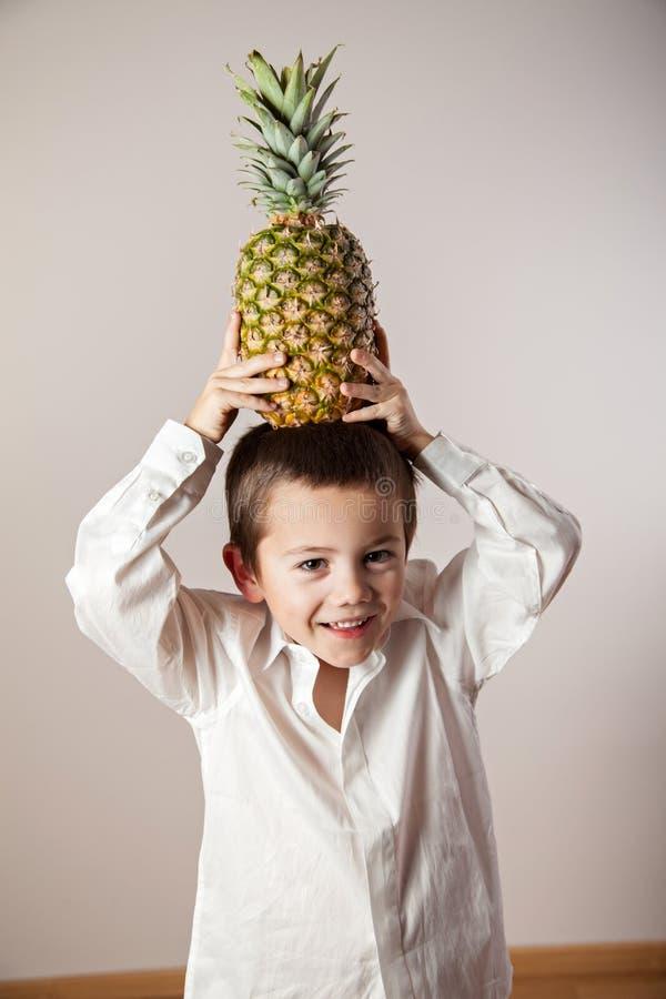 Froher Junge mit einer Ananas auf seinem Kopf lizenzfreie stockfotografie