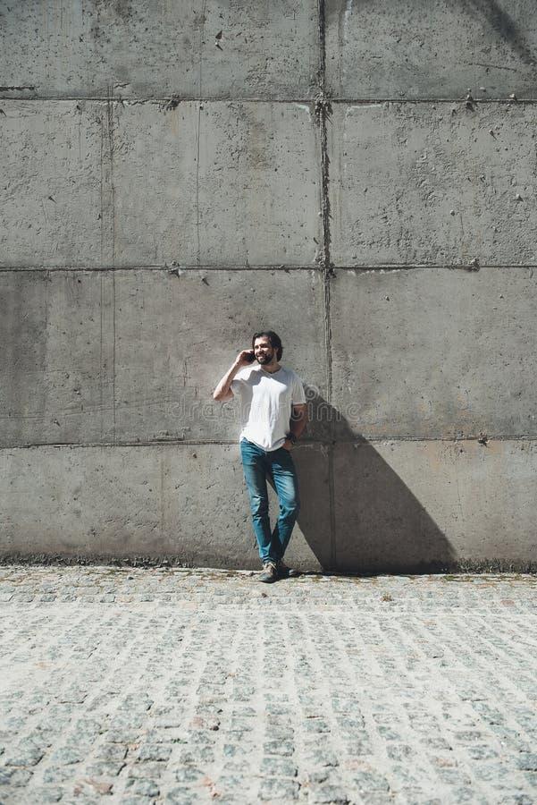 Froher Kerl, der draußen Handydialog genießt stockfoto