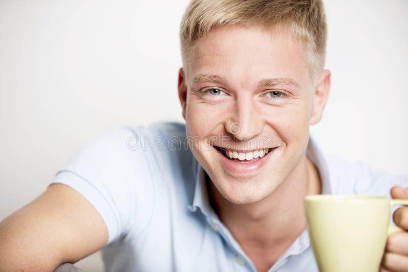 Froher lachender junger Mann, der einen Tasse Kaffee genießt. lizenzfreies stockfoto